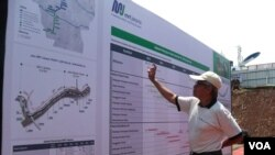 Seorang warga mengamati peta rencana pembangunan tahap awal rute MRT di Jakarta (VOA/Iris Gera)