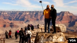 Visitors to the Grand Canyon take selfies with a cell phone on Dec. 6, 2019. (Photo by Hai Do)