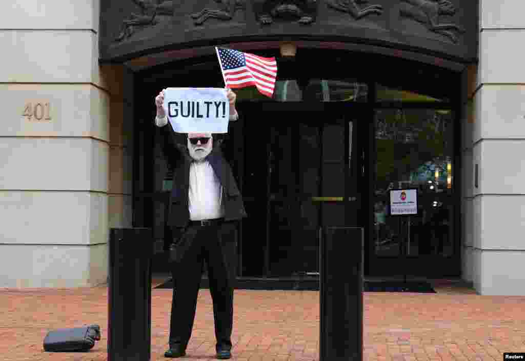 After a guilty verdict on the first count, an unidentified man holds a sign outside the U.S. District Courthouse in Alexandria, Virginia, Aug. 21, 2018, for the fourth day of jury deliberations in former Trump campaign manager Paul Manafort's trial on bank and tax fraud charges.