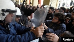 FILE - Demonstrators scuffle with riot police officers during a protest against home auctions in Thessaloniki, Greece, Nov. 29, 2017.
