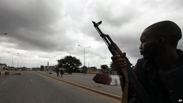"""A pro-Ouattara fighter from a group which calls itself the """"invisible commandos"""" patrols a street in northern Abidjan's Abobo district (Mar 26 2011"""