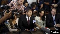 Wakilan gidan telebijin na Al-Jazeera, Mohamed Fahmy,a tsakiya, da Baher Mohamed, a hagu, su na magana da 'yan jarida tare da lauyansu.