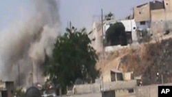 This image made from amateur video released by the Shaam News Network and accessed Wednesday, June 20, 2012, purports to show smoke rising from buildings in Homs province, Syria.