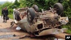 Nhân viên kiểm lâm Thái đứng cạnh đống đổ nát của một chiếc xe tải bị trúng bom vệ đường của quân nổi dậy Hồi giáo trong huyện Saiburi của tỉnh Pattani, miền nam Thái Lan, tháng 5, 2013. Các nhà phân tích của Nhóm Khủng hoảng Quốc tế cho biết trong 6 tháng đầu năm nay trung bình mỗi tháng có 24 vụ tấn công bằng bom mìn.