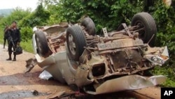 Seorang petugas berdiri di dekat truk yang hancur setelah melindas bom pinggir jalan di wilayah Saiburi, provinsi Pattani, Thailand (24/5). Dilaporkan lima tentara tewas dan satu terluka dalam insiden ini.