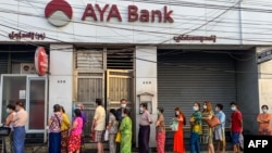 People wait for a branch of the AYA Bank to open, ahead of a long holiday stretch for the Myanmar New Year, also known as Thingyan, in Yangon on April 12, 2021, as the country remains in turmoil after the February military coup. (Photo by STR / AFP)
