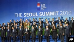 Members of the G20 wave during the family photo session at the G20 Summit in Seoul. Leaders of the world's 20 biggest economies faced the urgent task at their summit Friday of resolving a U.S.-China currency dispute that has raised the specter of a global
