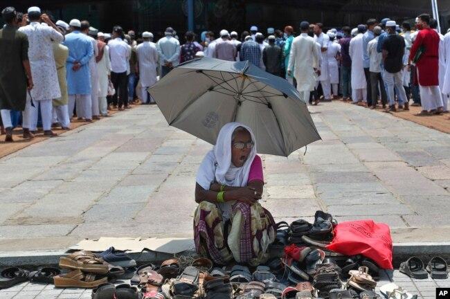 Seorang perempuan duduk di bawah naungan payung dan mengawasi alas kaki para jemaah yang datang untuk salat Jumat terakhir di bulan suci Ramadan, di Masjid Mekah, Hyderabad, India, Jumat, 7 Mei 2021. (AP)