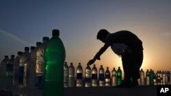 在卡拉奇的一个海滩上,一个男孩在整理他所出售的饮用水