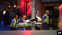 Một con tin bị thương được cảnh sát đưa ra xe cứu thương sau khi có nhiều phát súng nổ trong 1 vụ bắt cóc ở 1 tiệm cafe ở Martin Place ở quận trung tâm thương mại của Sydney, Australia, hôm 16/12.