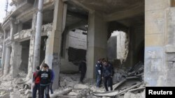 Residents inspect damage from what activists said was by warplanes loyal to Syria's President Bashar al-Assad in Jibb al-Quebeh neighborhood in Aleppo, April 11, 2015.