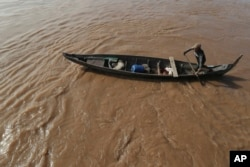 FILE - A Cambodian Muslim man rows his wooden boat where he lives along the Mekong River bank at a fisherman floating village located in Kball Chroy, near Phnom Penh, Cambodia, on Monday, Sept. 9, 2019. (AP Photo/Heng Sinith)