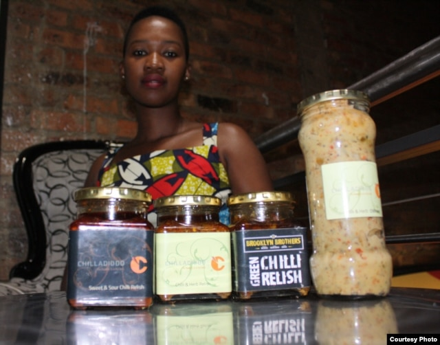 Farmer Leeko Nkala shows off a few of the sauces she produces from chili crops grown in South Africa's North West Province.