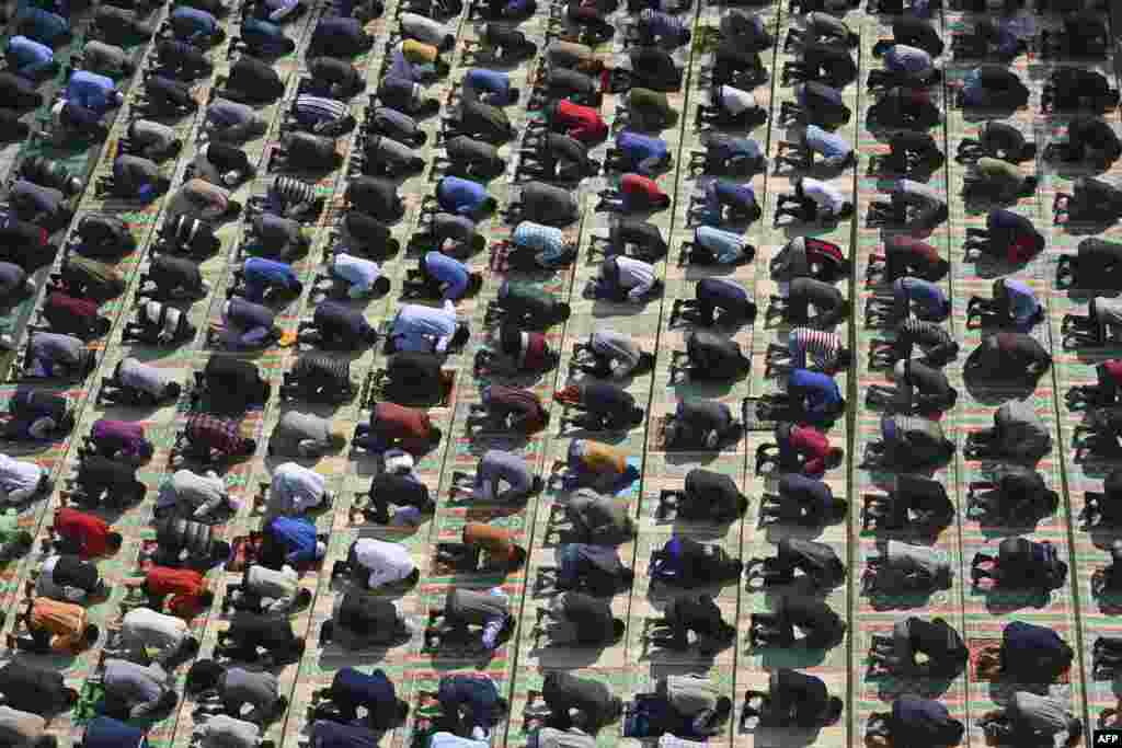 Kashmiri Muslims offer Friday prayers on the banks of the Jhelum River while maintaining social distancing as a preventative measure against COVID-19, in Srinagar, India.