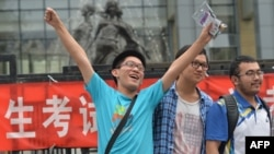 """A student pose for a photo after taking the 2014 college entrance exam of China, or the """"gaokao"""", outside a high school in Beijing, June 8, 2014."""