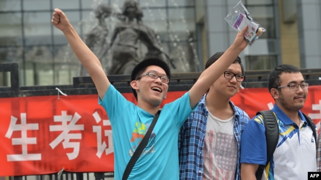 "A student pose for a photo after taking the 2014 college entrance exam of China, or the ""gaokao"", outside a high school in Beijing, June 8, 2014."