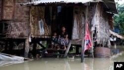 在緬甸一位婦女和她的孩子無奈的看著洪水淹沒到她居所的一半。