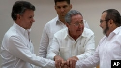 Cuba's President Raul Castro (Center) encourages Colombian President Juan Manuel Santos (Left) and Commander the Revolutionary Armed Forces of Colombia or FARC, Timoleon Jimenez, to shake hands, in Havana, Cuba, Sept. 23, 2015.