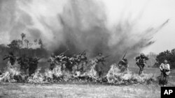 Ranger Troops of the U.S. Army demonstrate charging through a wall of fire as land mines explode behind them during maneuvers at Camp Rucker, Ala., March 5, 1943. (AP Photo)