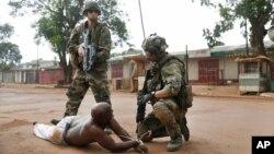 Dua tentara Perancis menahan salah seorang pendukung Seleka di Bangui (9/12). Perancis kehilangan dua tentaranya dalam pertempuran di Bangui.