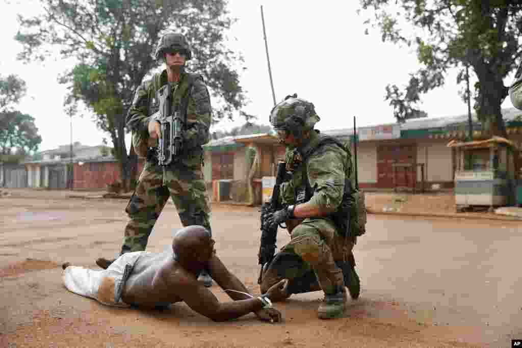 French troops detain a suspected Seleka officer, preventing Christian mobs from lynching him near the airport in Bangui, Central African Republic, Dec. 9, 2013.