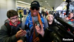 FILE - Former NBA basketball player Dennis Rodman talks to the media at the Beijing International Airport.