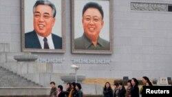 1일 평양 김일성 광장에 걸려있는 김일성.김정일 초상화 앞을 지나는 북한 주민들.