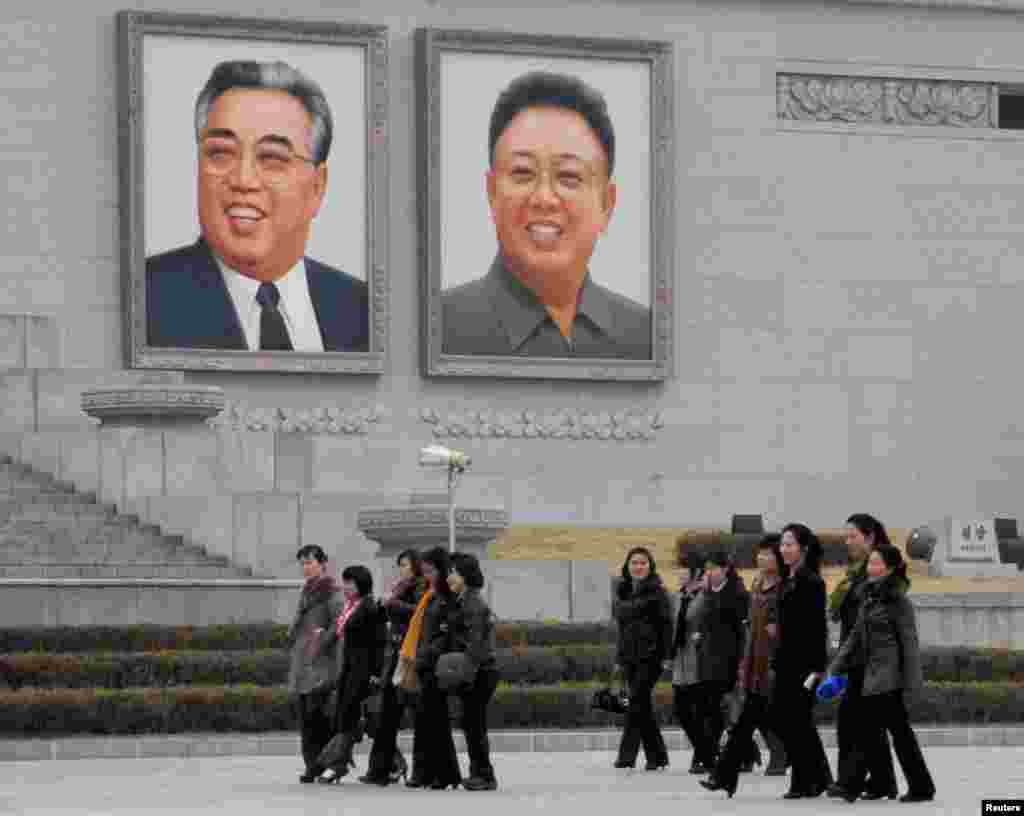 North Korean women walk in front of portraits of North Korea's founder Kim Il-sung (L) and late leader Kim Jong-il at Kim Il-sung Square in Pyongyang, in this photo provided by Kyodo, April 1, 2013.