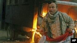 11月19日开罗的一名抗议者手持国旗,身后是一辆被示威者点燃的警车