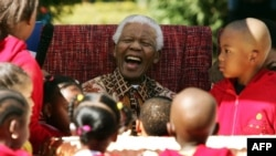 Nelson Mandela jariko atera ibinaga n'abana mu gisagara ca Johannesburg mu mu mwaka w'2007.