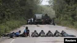 ຕໍາຫລວດ ແລະທະຫານໄທ ຕັ້ງທ່າຍິງ ໃນຂະນະທີ່ຊອກຫາ ວັດຖຸລະເບີດ ຢູ່ໃນບ້ານ Raman ລຸນຫລັງທີ່ ຊາວນາກຸ່ມນຶ່ງ ບອກວ່າ ພວກເຂົາເຈົ້າພົບເຫັນກິດຈະກໍາທີ່ໜ້າສົງໄສ ຢູ່ແຂວງ ຢາລາ ທາງພາກໃຕ້ຂອງປະເທດໄທ, ວັນທີ 8 ກຸມພາ 2013. (Reuters)
