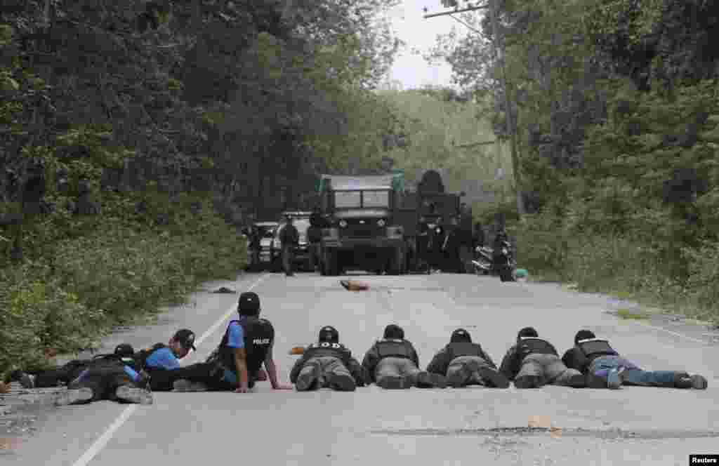 Thai policemen and soldiers take up position during a search for explosives in the village of Raman after local farmers alerted them to suspicious activities in Yala province, south of Bangkok, Thailand.