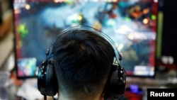 A man plays online game on a computer at an internet cafe in Beijing, China August 31, 2021. (REUTERS/Florence Lo)