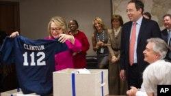 """美國國務卿克林頓1月7號返回國務院的工作崗位﹐獲送印有國務院徽章的美式足球球衣與頭盔。球衣上印上""""112""""得字樣﹐表示她任內走訪112個國家。"""