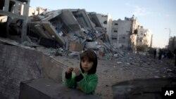 ایک فلسطینی بچی اسرائیلی طیاروں کی بمباری میں تباہ ہونے والے حماس کے الاقصیٰ ٹیلی وژن اسٹیشن کے قریب کھڑی ہے۔ 13 نومبر 2018