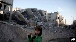 Seorang bocah Palestina berdiri di samping reruntuhan gedung stasiun TV Al-Aqsa Hamas yang terkena serangan udara Israel.(13/11)