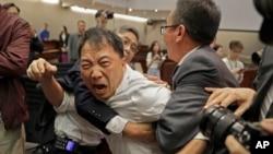 Nhà lập pháp thân dân chủ Hồ Chí Vỹ, ở giữa, xô xát với nhân viên an ninh tại Hội đồng Lập pháp Hong Kong. Tình hình tại nghị viện HK trở nên hỗn loạn trong bối cảnh cuộc đối đầu giữa bên chống, bên ủng hộ luật dẫn độ, ảnh chụp ngày 11/5/2019. (AP Photo/Vincent Yu)