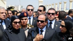 In this picture taken June 30, 2015, and provided by the office of the Egyptian Presidency, Egyptian president Abdel-Fattah el-Sissi (C) speaks at the funeral for Hisham Barakat, surrounded by the latter's family members.