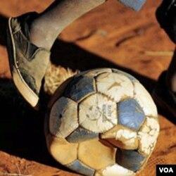 Seorang anak bermain sepak bola di tengah-tengah jalan berdebu di kota Soweto.