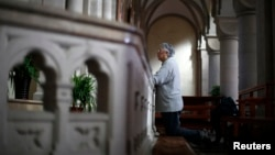 FILE - A woman prays at Sheshan Cathedral in the outskirts of Shanghai October 28, 2013. Picture taken on October 28, 2013.