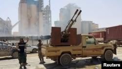 FILE - Members of forces loyal to Libya's eastern government stand near to the Libyan cement factory after the army took control of the factory following clashes with the Les membres des forces loyales au gouvernement de l'Est de la Libye aperçus près de l'usine de ciment libyen dont l'armée a pris le contrôle après des affrontements avec le Conseil de la Choura des révolutionnaires libyens, une alliance d'anciens rebelles anti-Kadhafi qui ont uni leurs forces avec le groupe islamiste Ansar al -Sharia, à Benghazi, en Libye 18 Avril 2016. REUTERS / Stringer - RTX2AHYZShura Council of Libyan Revolutionaries, an alliance of former anti-Gaddafi rebels w