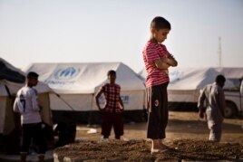A boy, who fled from the violence in Mosul, stands near tents in a camp for internally displaced people on the outskirts of Arbil in Iraq's Kurdistan region, June 14, 2014.