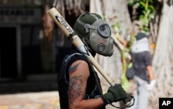 A protester uses a baseball bat and gas mask during clashes with security forces blocking an opposition march from reaching the National Electoral Council headquarters in Caracas, Venezuela, May 24, 2017.