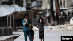 FILE - Children eat corn on the cob on a street in Douma, eastern al-Ghouta, near Damascus.