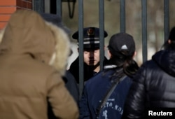A security guard is pictured through the gate at the kindergarten run by pre-school operator RYB Education Inc being investigated by police, in Beijing, China, Nov. 24, 2017.
