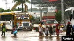 Habitantes de un barrio de Acapulco evacúan el lugar por temor a las inundaciones provocadas por la tormenta Manuel.