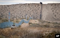 FILE - A U.S. Border Patrol agent drives near the U.S.-Mexico border fence in Sunland Park, N.M. The building of a border wall was one of the main tenets of the Donald Trump campaign.