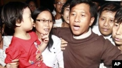 Jim Mee, right, and Nilar Thein, center, activists of the 88 Generation Students Group, gets welcomed by their daughter, left, at Yangon airport after being released from prison Friday, Jan.13, 2012.