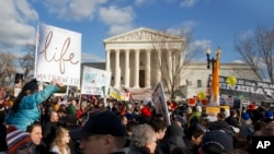 Anti-abortion demonstrators march past the Supreme Court in Washington, Thursday, Jan. 22, 2015.