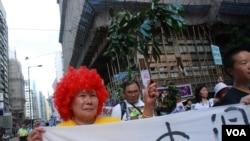 65歲的古洞居民陳婆婆,帶著紅色假髮參加遊行,波浪頭髮代表陳茂波,要求他下台 (美國之音湯惠芸拍攝)